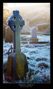A rimfrosted Celtic cross glows in the sunrise.